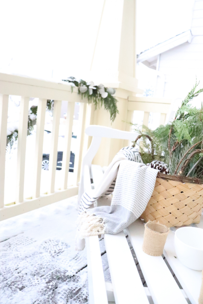 Mountain Farmhouse Winter Porch Decor Tips  winter porch decor, winter basket with greens and tea towels, burlap wrapped tea lights, garland, front door DIY wreath, birchwood logs, fire logs, winter candles, warm and welcoming front porch