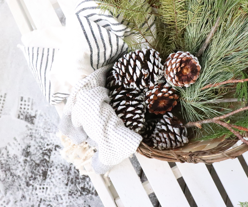 Mountain Farmhouse Winter Porch Decor Tips  pinecones, winter basket with greens and tea towels, burlap wrapped tea lights, garland, front door DIY wreath, birchwood logs, fire logs, winter candles, warm and welcoming front porch