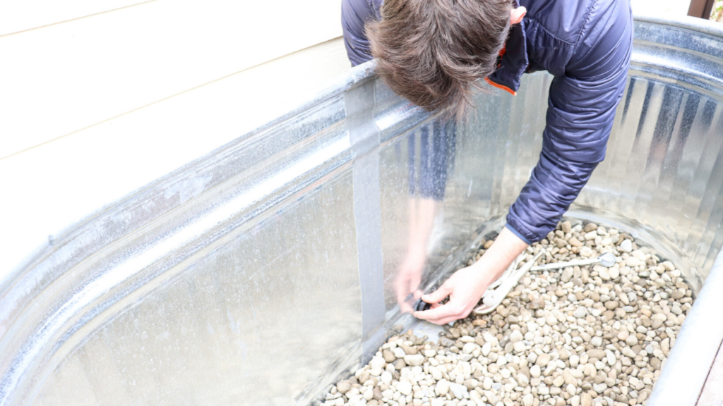 stopping the built-in drainage hole in the galvanized horse trough planter box on cedar wood stand
