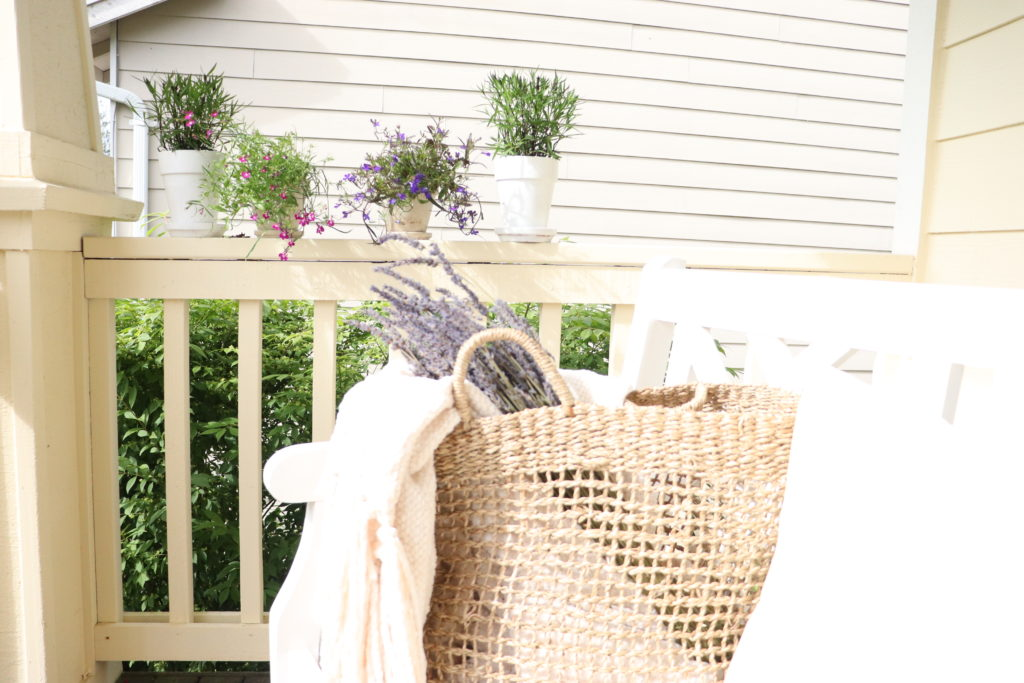 flowers and a woven basket with lavender in the farmhouse garden front porch